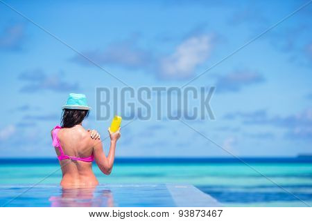 Young woman applying sun cream during beach vacation