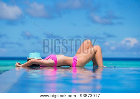 Young beautiful woman enjoying summer vacation in luxury swimming pool