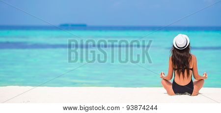 Young woman sitting in yoga position during tropical vacation