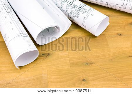 Rolls Of Blueprints On Wooden Desk