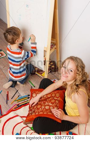 Young woman sitting in children room with her son drawing