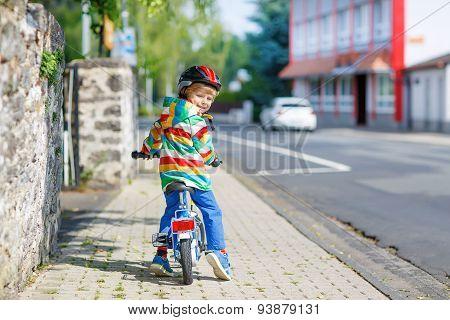 Kid Boy In Helmet Riding His First Bike, Outdoors