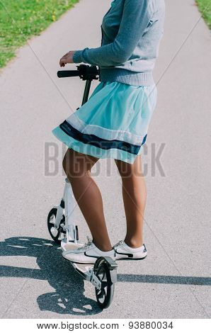 Legs Of Young Woman On Kick Scooter