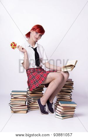 Girl With Lollipop Sitting On A Pile Of Books