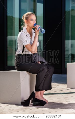 Businesswoman Drinking Water From A Small Bottle