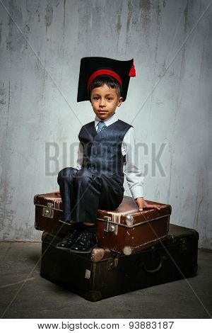 small black boy in  graduation hat sits on the old suitcases