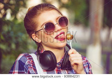 Hipster Girl Licking Lollipop. Headphones.