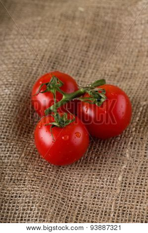 Three Wet Cherry Tomatoes On Jute Cloth