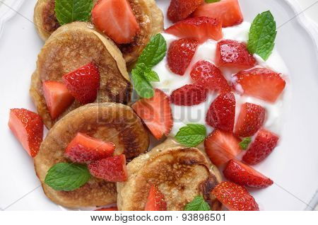 Pancakes with yogurt, fresh strawberries and mint
