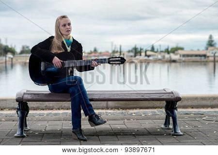 Cute Blonde Playing Guitar While Sitting On A Bench