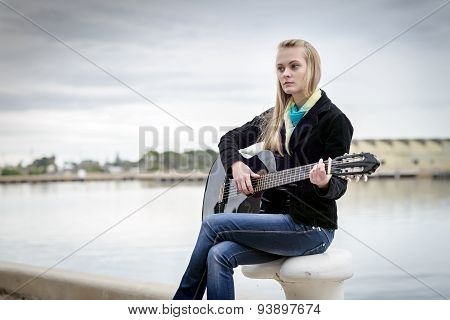 Cute Blonde Playing Guitar While Sitting On The Bitt