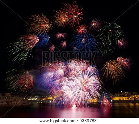 Red pink colorful fireworks explode in Malta in dark sky,Malta fireworks festival,Independence