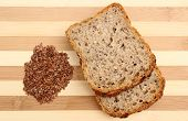 image of cutting board  - Linseed on cutting board with slices of wholemeal bread - JPG