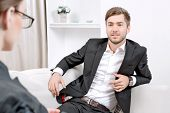 picture of clipboard  - Young man wearing a black suit sitting on a couch looking at his doctor and listening - JPG