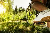 image of pedal  - shoe on the bike pedal in front of bloomy sunny nature background