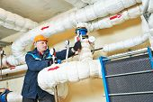stock photo of engineer  - repairman engineer of fire engineering system or heating system open the valve equipment in a boiler house - JPG