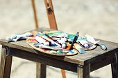 picture of paint palette  - Wooden stand with palette and paint on beach - JPG