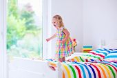 stock photo of little young child children girl toddler  - Children jump on a bed - JPG