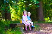 stock photo of little young child children girl toddler  - Kids sit on a bench in a park - JPG