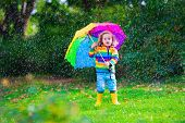 stock photo of rain  - Child with colorful umbrella playing in the rain - JPG