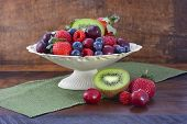 stock photo of fruit bowl  - Summer Fruit including raspberries strawberries cherries blueberries and kiwi fruit in a vintage bowl with reclaimed dark wood background - JPG