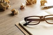 foto of stress-ball  - Crumpled paper balls with eye glasses and notebook on wood desk with soft light - JPG