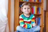 picture of daycare  - Little blond kid boy sitting in front of bookcase indoors - JPG