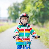 pic of four-wheel  - Happy funny kid boy of 4 years and colorful raincoat riding his first bike on summer day - JPG