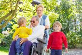 foto of grandfather  - Two little kid boys their grandmother and grandfather in wheelchair in summer garden - JPG