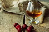 picture of black-cherry  - Brandy glass and black cherry horizontal selective focus - JPG