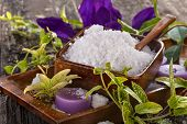 stock photo of salt-bowl  - salt bath in wooden bowl with flowers and leaves in background - JPG