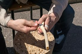 stock photo of woodcarving  - Traditional woodcarver whittling wood with a carving knife - JPG