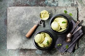 picture of mint-green  - Green tea ice cream with mint leaves and Spoon for ice cream on stone slate background - JPG
