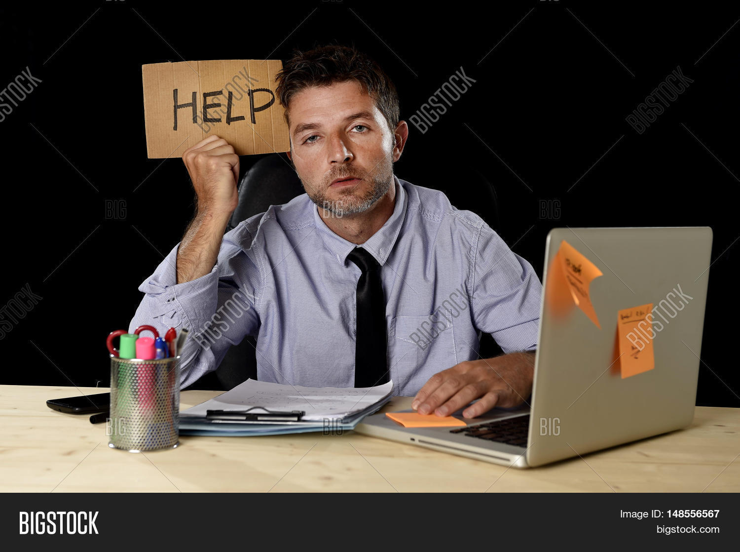 young desperate businessman suffering stress working at office young desperate businessman suffering stress working at office computer desk holding sign asking for help looking
