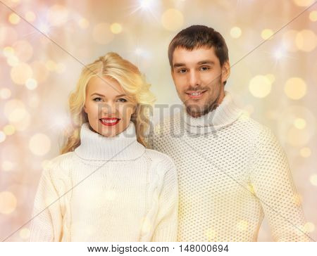 people, christmas, holidays and new year concept - happy family couple in winter clothes over holidays lights background
