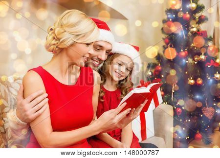 family, christmas, x-mas, winter, happiness and people concept - smiling family in santa helper hats with many gift boxes reading book
