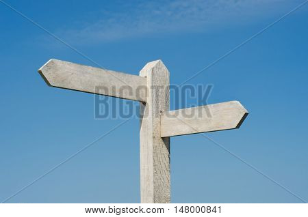 Old wooden signpost with two blank boards pointing in different directions weathered to white against bright blue sky with light fluffy clouds.