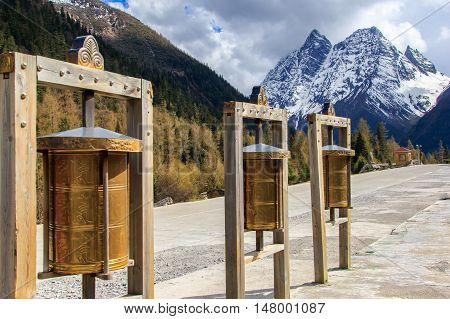 Maiden's Mountain Scenic Area is an unspoiled wilderness park located in western china and Qiang Autonomous Prefecture at Prayer wheels foreground Sichuan Province China. selective focus