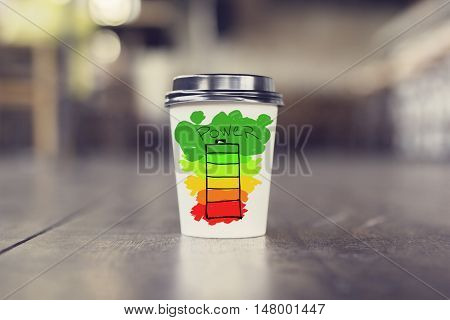 Takeaway coffee cup with colorful battery on wooden floor. Energy concept