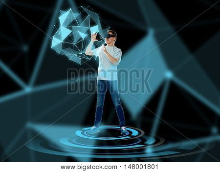 3d technology, augmented reality, gaming, cyberspace and people concept - happy young man with virtual reality headset or 3d glasses playing game and touching low poly shape hologram
