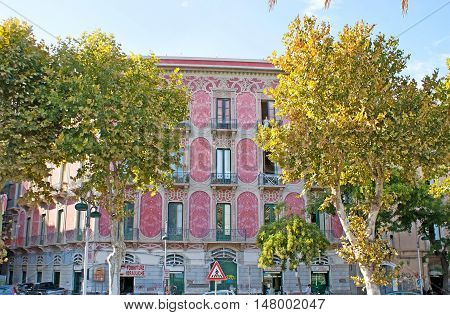 CATANIA ITALY - OCTOBER 10 2012: The beautiful mansion painted in bright pink color and decorated with patterns and reliefs on October 10 in Catania.