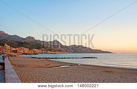 The romantic sunrise over the central beach of Giardini Naxos with the view on the sharp rocks of Taormina Sicily Italy.