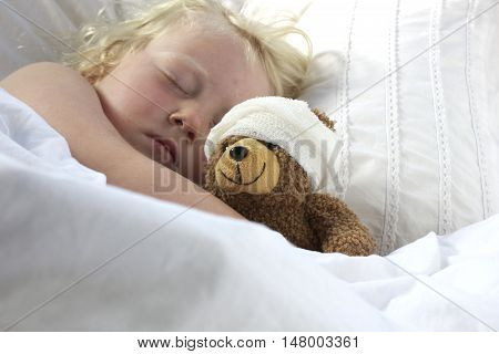 A young girl poorly in bed cuddling her teddy who also feels poorly.