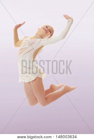Beautiful little girl gymnast dressed in sports swimsuit, jumps high.On a purple background.