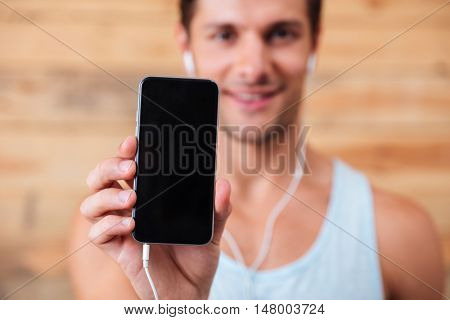 Cheerful young man in earphones showing blank screen cell phone over wooden background