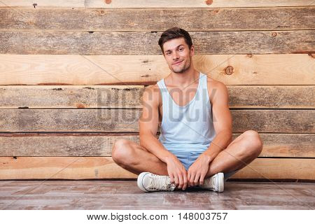 Happy casual man sitting on the floor with legs crossed over wooden background