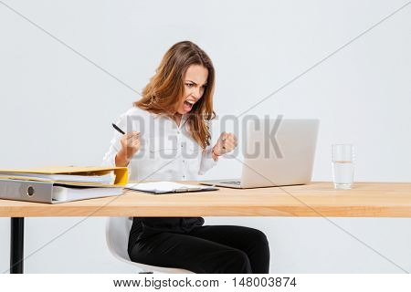 Angry young businesswoman using laptop and shouting over white background