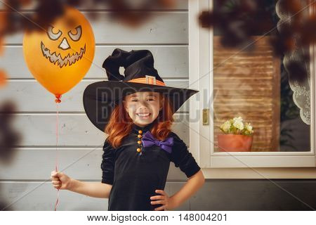 Happy Halloween! Cute cheerful little witch outdoors. Beautiful child girl in witch costume near house decorated to Halloween.