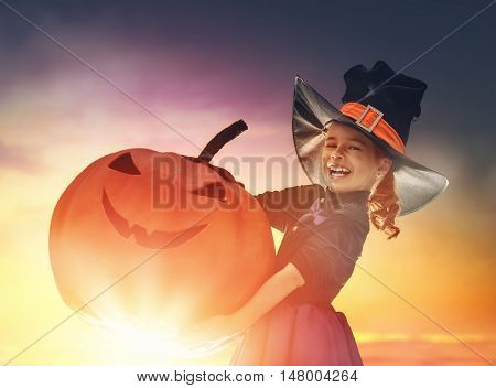 Happy Halloween! Cute little witch with a big pumpkin. Beautiful young child girl in witch costume outdoors.