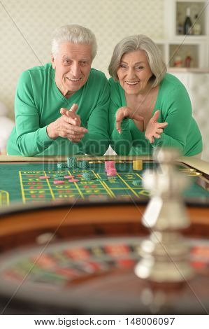 happy Senior couple playing with casino chips